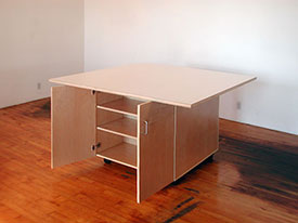Tables for the art studio roll on wheels with cabinets below for storing art.