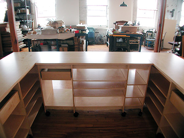 U-shaped art work station with storage shelves and drawers for art papers, art supplies, and finished artwork.