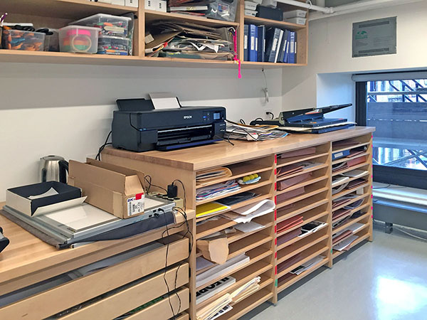Photography Studio Furniture by Art Boards™ in School photo studio has a long deep counter space for photography equipment, with adjustable shelving and drawers below, and a long hanging book shelf above for storing needed supplies.
