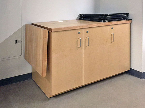 Drop leaf under counter hardware provides full access to butcher block counter folds down out of the way to provide full access electrical panel in the art studio classroom for photography.