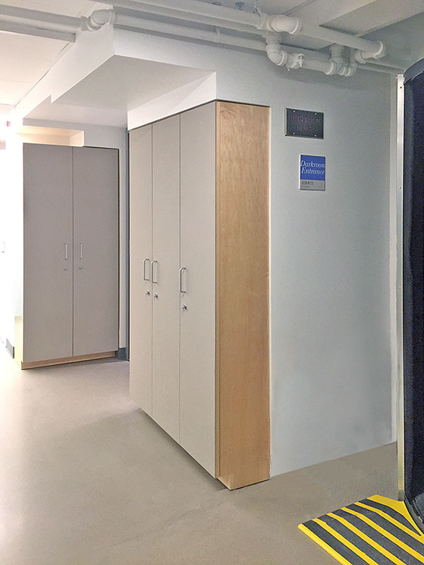 Photography storage cabinets are located next to the school photo studio classroom and the analog photography darkroom.