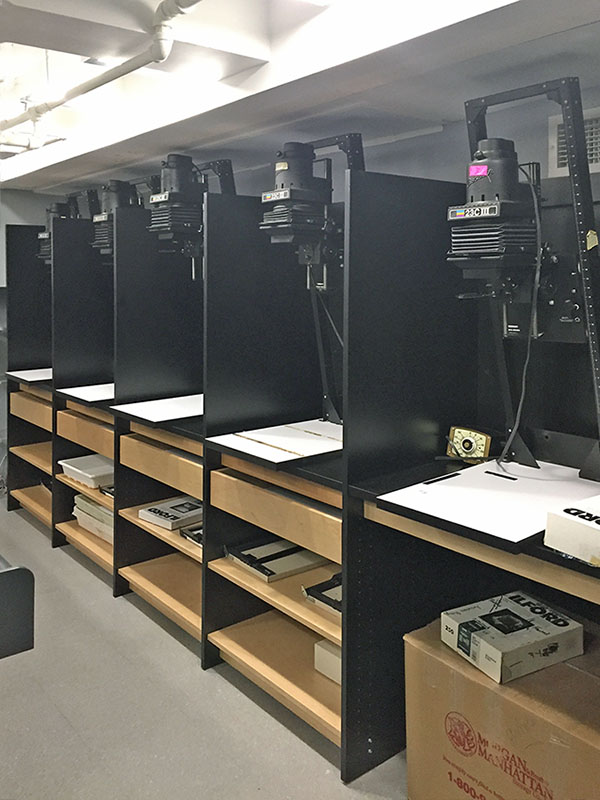 Artist darkroom showing 5 photo enlarger stations along walll in art school darkroom with photography cabinets, drawers, and storage shelves below.