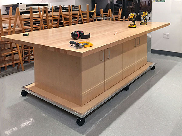 Photography art studio furniture is mobile. This art studio work table is 4' x 8', it rolls on wheels, and has cabinet storage below behind doors. It is made for art studios, photography classrooms, and art schools. Fabricated and distributed by Art Boards™ in Brooklyn New York.