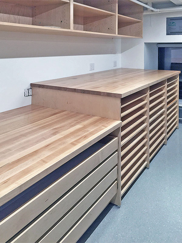 Deep maple butcher block counters in school photo studio has oversize drawers and deep open shelving for each photography student.