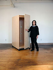Art Storage Cabinet with locking doors is mobile on wheels.